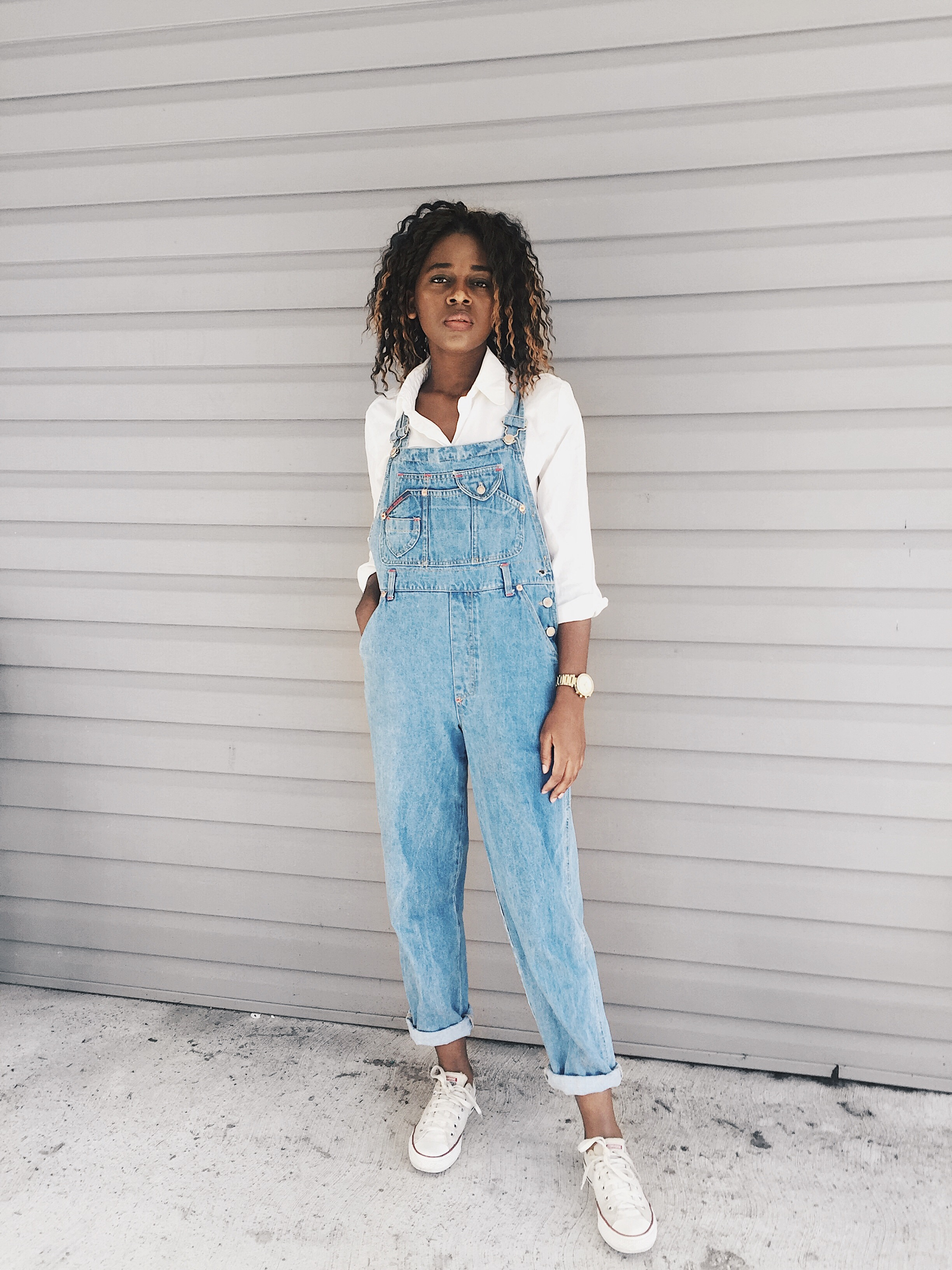 white button down shirt, light wash denim overalls, white chucks converse